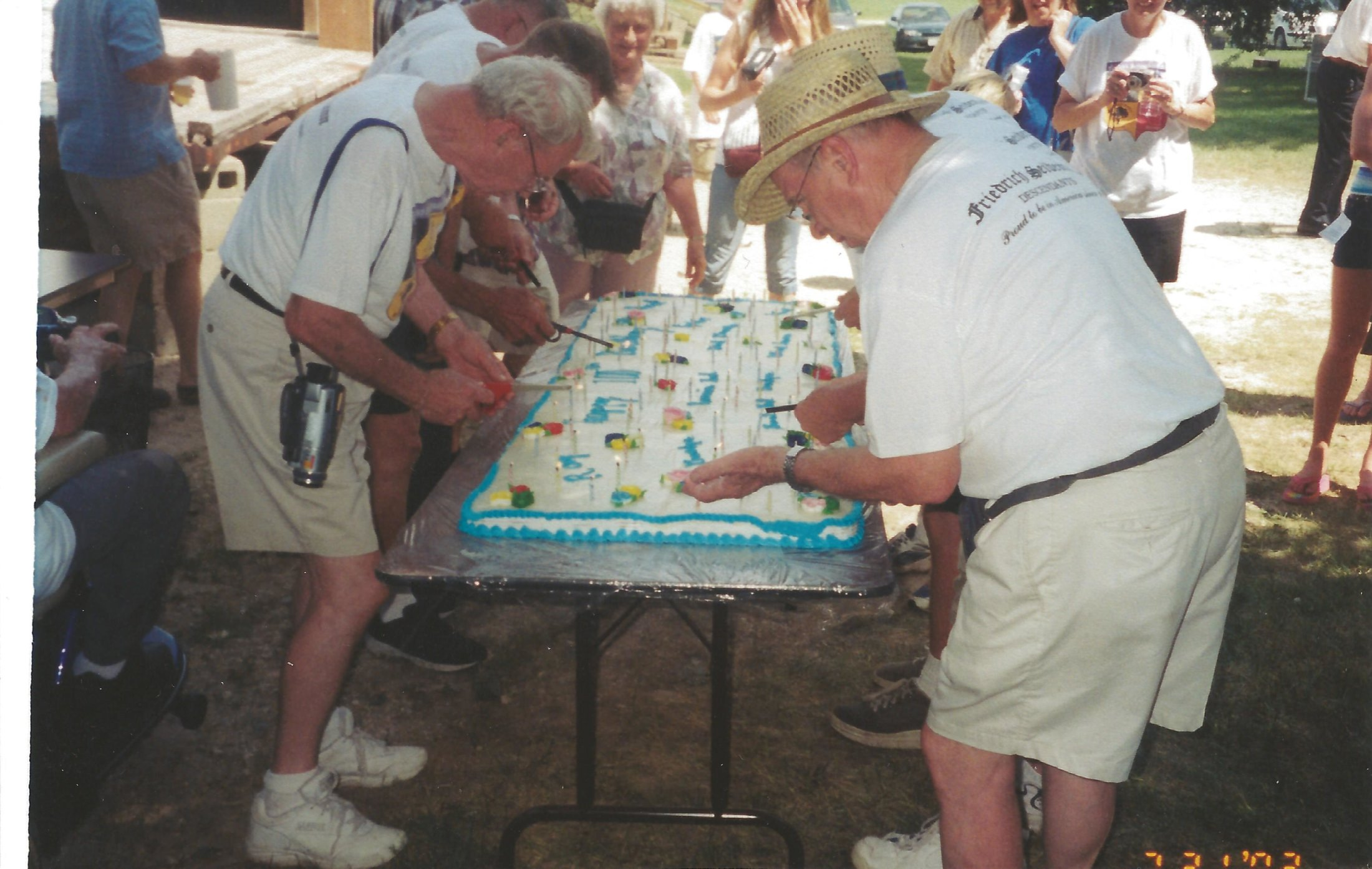 Ray's sons lighting the 100 Candles on Ray's Birthday Cake